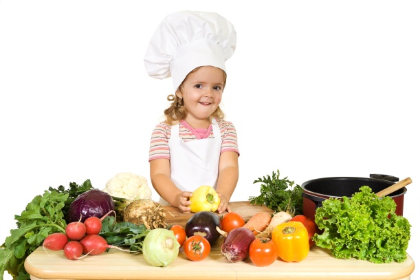 Happy little girl as a chef preparing vegetables for cooking